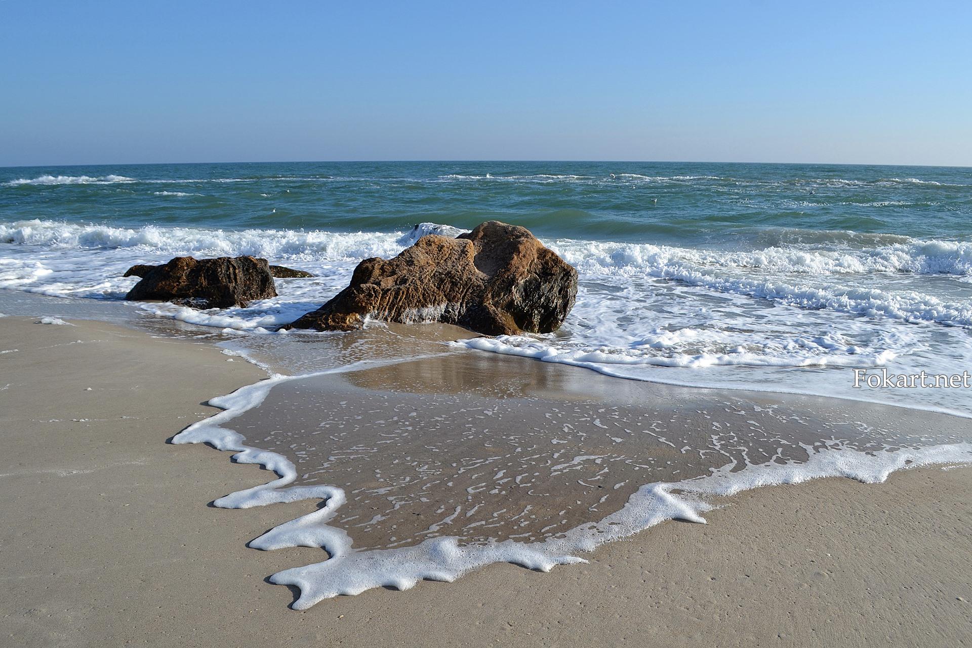 Волна с пенным гребешком на берегу, начавшая скатываться обратно