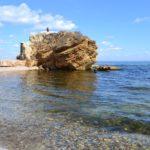 Чистая морская вода и большой жёлтый скалистый камень