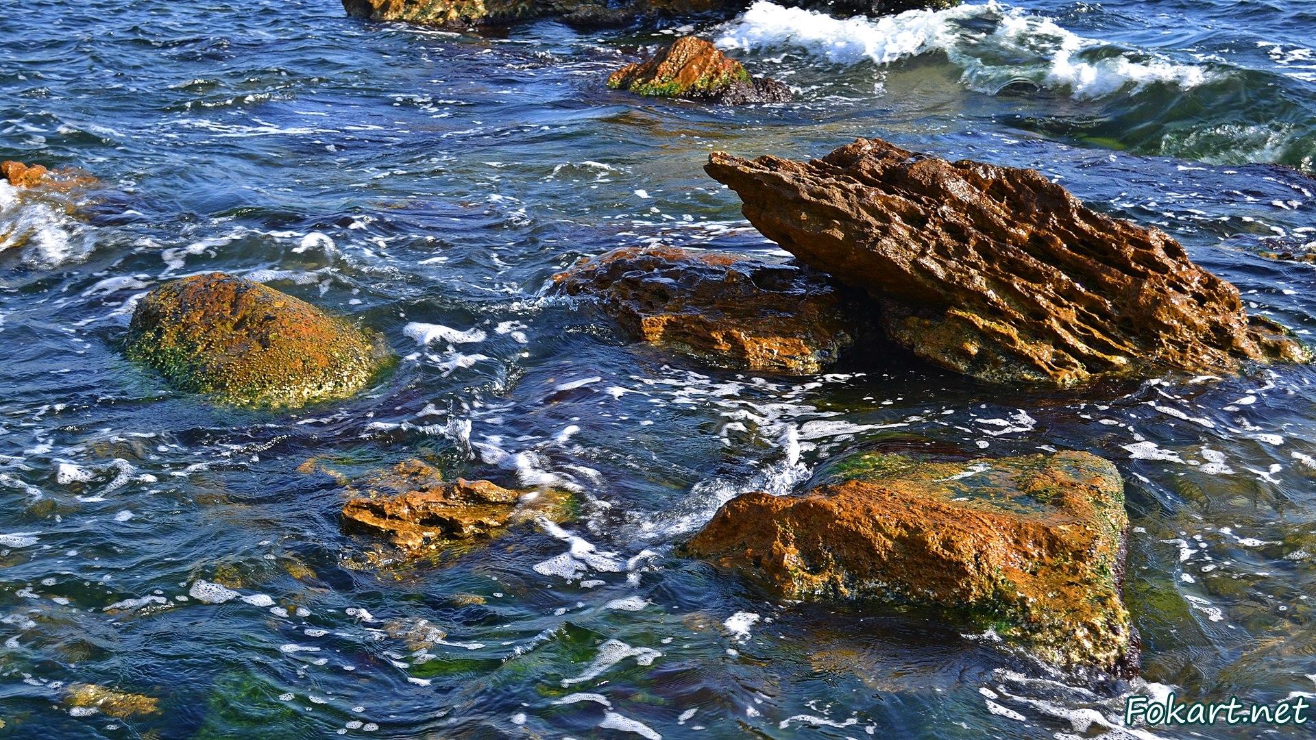 Крупные скалистые камни на мелководье у берега