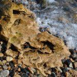 Причудливый большой камень среди мелких камешков