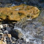 Чистая, прозрачная вода волны у каменистого берега
