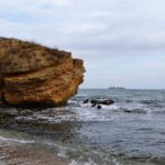 Большой жёлтый скалистый камень у самого берега