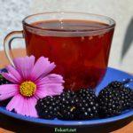 Прозрачная чашка чая с добавлением свежих плодов ежевики и цветок космеи.