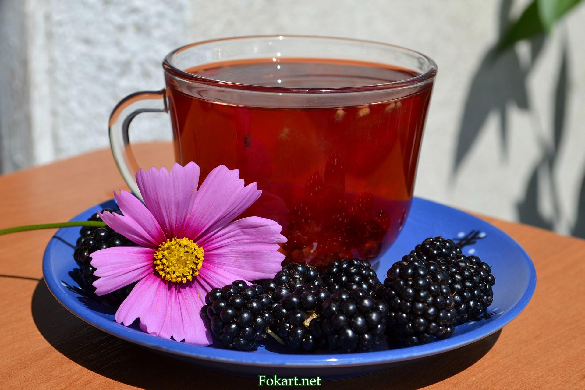 Чашка чая с добавлением свежих плодов ежевики и цветок космеи