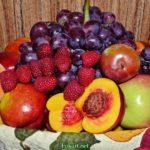 Ягоды малины, виноград, персики, нектарины, яблоки и сливы в корзинке