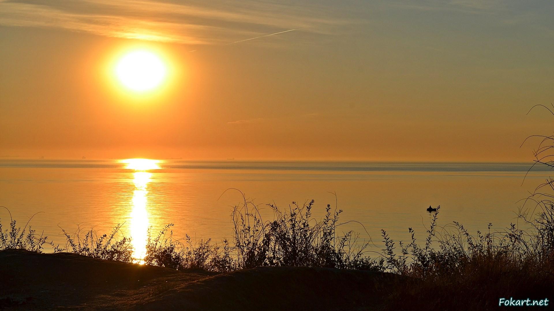 Летний рассвет над морем. Солнце, солнечная дорожка на воде, одинокая лодка и оранжевые краски неба.