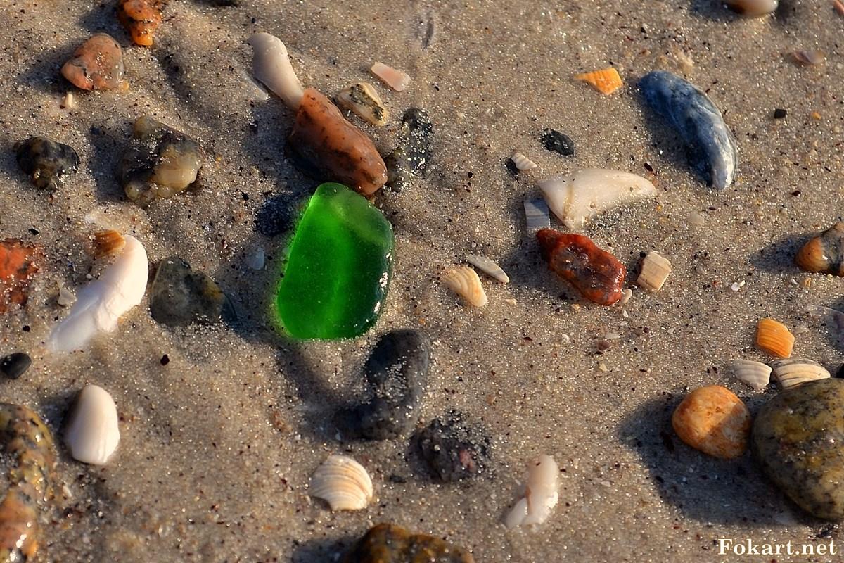 Морские камешки на мокром песке после отхода волны
