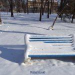 Заснеженная скамейка и сугробы в парке после сильного снегопада